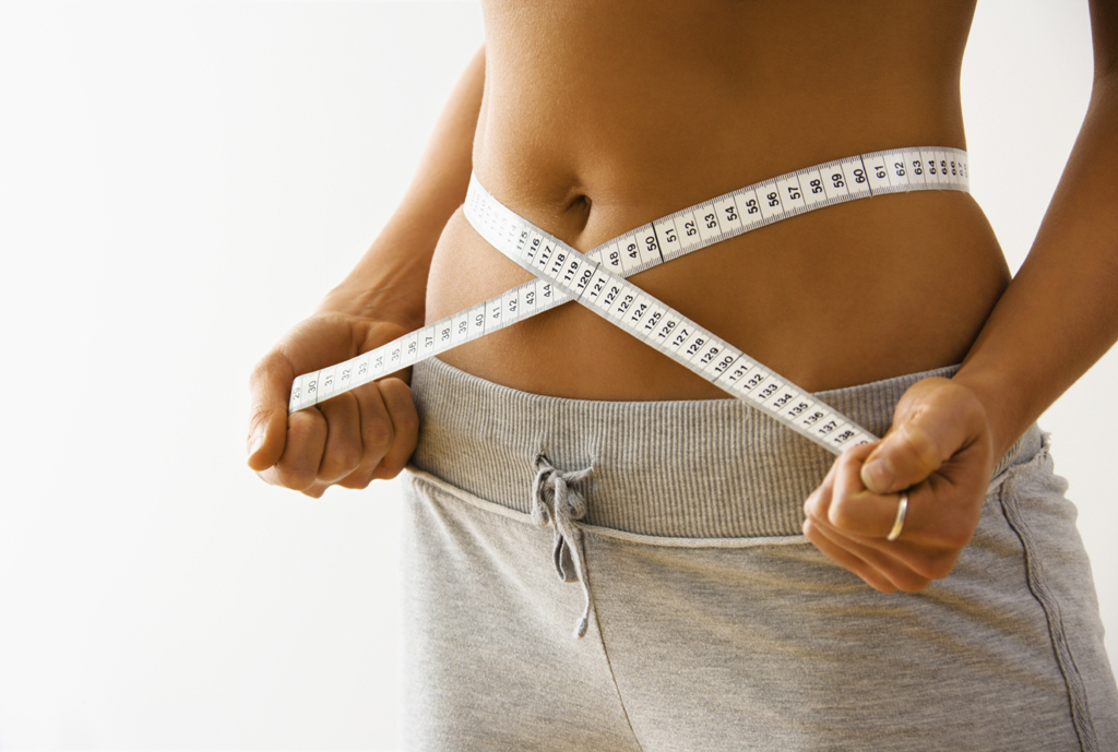 Woman standing pulling measuring tape around waist.